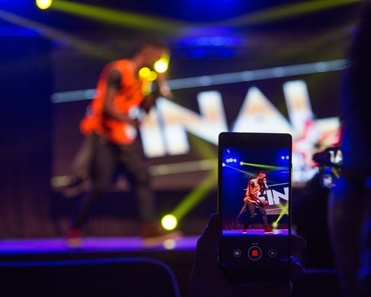 A spectator records video as a contestant performs during the final of Zimbabwe's Dreamstar 2015 talent show, in Harare Oct. 31, 2015. The show, organized by local Chinese community, provides an opportunity to thousands of Zimbaweans pursuing their dreams on stage. (Xinhua/Xu Lingui)