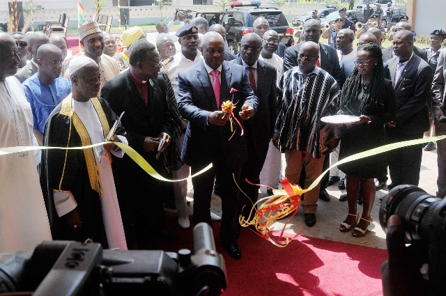 Ghana's President John Dramani Mahama cuts the ribbon during the opening ceremony of the refurbished parliamentary office in Accra, capital of Ghana, on Nov. 6, 2015. China's State Hualong Construction Ghana Limited handed over here on Friday the completed refurbished office structure to Ghana's parliament. (Xinhua/Lin Xiaowei)