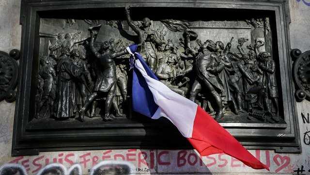 A French national flag is seen on the monument at the Place de la Republique square to mourn for the victims of the terrorist attacks in Paris, capital of France, Nov. 15, 2015. (Xinhua/Zhou Lei)(azp)