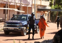 Photo taken on Nov. 20, 2015 shows a freed hostage leaves with the help of the police in Bamako, Mali. At least 80 people taken hostage by unidentified gunmen in Radisson Hotel in the Malian capital Bamako have been freed, according to the Malian security ministry. (Xinhua)