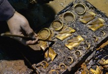 An archaeologist cleans the hoof-shaped ingots in an aristocrat's tomb that dates back to the Western Han Dynasty (206 BC - 24 AD), in Nanchang, capital of east China's Jiangxi Province, Nov. 17, 2015. Chinese archaeologists on Nov. 17 discovered 75 gold coins and hoof-shaped ingots in the tomb. (Xinhua/Wan Xiang)