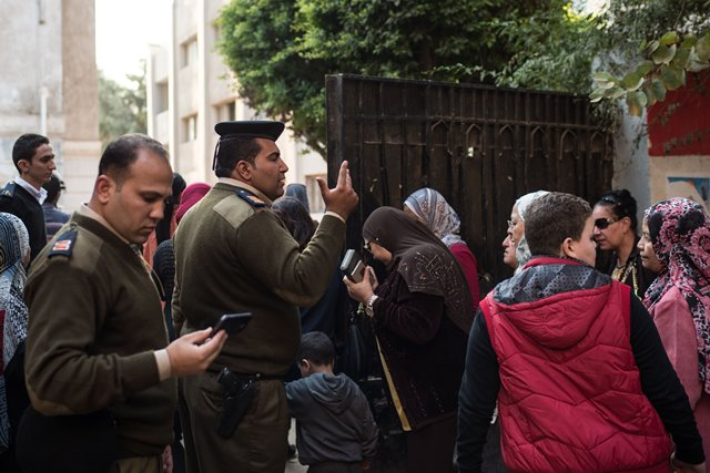 Egyptian policemen guide voters to enter a polling station for women in Cairo, Egypt, on Nov. 22, 2015. Egyptians began voting Sunday in the second phase of the country's first parliamentary election since Islamist President Mohamed Morsi was ousted in 2013. (Xinhua/Pan Chaoyue)