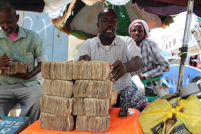 A man displays money at the exchange market in Suq Bacad market in Mogadishu, Somalia, Nov. 18, 2015. (Xinhua/ Faisal Isse)