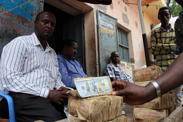 Businessmen display money at the exchange market in Suq Bacad market in Mogadishu, capital of Somalia, Nov. 18, 2015. (Xinhua/Faisal Isse)