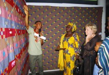 Mr Ahiagble Bob Dennis showing the various type of Kente to Madam Gomashie and the Norwegian Ambassador