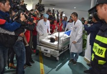 Tian Zeming, a survivor found in the landslide site, is surrounded by reporters after receiving a surgical debridement at the Guangming New District Central Hospital in Shenzhen, south China's Guangdong Province, Dec. 23, 2015. Tian was pulled out alive early Wednesday morning more than 60 hours after a landslide hit an industrial park in Shenzhen and rushed to the hospital. (Xinhua/Mao Siqian)