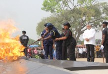 ACP Nuhu Jango lighting the perpetual flame; while former President Jerry John Rawlings (in white top) looks on.
