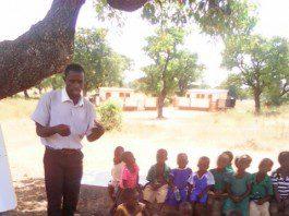 Kaase Primary School teacher teaching Kindergarten children under a tree