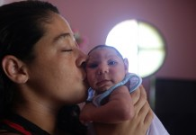 Pollyana Rabello (L) kisses her baby Luiz Philipe, who was born with microcephaly, at their house in Marica, Rio de Janeiro state, Brazil, on Feb. 4, 2016. Luiz Philipe was born on Dec. 28, 2015 with microcephaly and now lives with his family in Marica, Rio de Janeiro state, where 208 cases of microcephaly have been reported. The United Nations Population Fund (UNFPA) said on Thursday it was closely monitoring the outbreak of the Zika virus and warning about its potentially adverse effects on the health of women and babies, particularly in Latin America. (Xinhua/Daniel Castelo Branco/Agencia o Dia/AGENCIA ESTADO)(zhf) ***BRAZIL OUT***