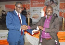 Edward Opare Donkor, the Chief Operating Officer, Fidelity Bank, presenting a gold coin to one of the winners.