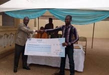 Mr David Norden Botwey, the Executive Director of SWEB Foundation, presenting a dummy cheque to one of the partner organisations at its Haatso officer, in Accra.