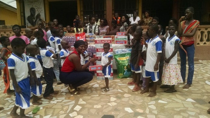 Ms Beatrice Yeboah Gyimah (left) presenting the items to one of the kids