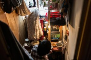 "AFP / Anthony Wallace A man watches television in his ""cubicle"" flat built within a subdivided ""rooftop house"", which he shares with other tenants on the roof of a residential building in Kowloon"