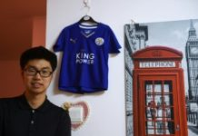 Leicester City fan Wang Song Aohan posing with a signed jersey in his apartment in Beijing