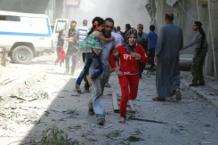 AFP / Ameer Alhalbi A Syrian family runs for cover amid the rubble of destroyed buildings following a reported air strike on the rebel-held neighbourhood of Al-Qatarji in the northern Syrian city of Aleppo, on April 29, 2016
