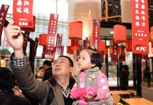 A father and his daughter take part in the riddle-guessing contest at a KFC outlet in Zhengzhou, capital of Henan Province, during this year's Lantern Festival. [Photo/China Daily]