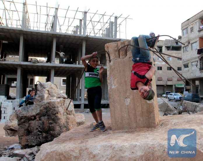 Children play near an abandoned building in the southern suburbs of Damascus, Syria, March 12, 2016. The Syrian civil war since March 2011 has made the Middle East country the world's single-largest source of refugees and displaced people, according to UN figures. The long-running conflict has claimed at least 250,000 lives and forced over 2 million children out of school. (Xinhua/Yang Zhen)