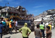 Residents stand in front of the debris of houses after an earthquake in the city of Chone, Manabi Province, Ecuador, on April 17, 2016. [Photo/Xinhua]