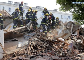 Rescuers search for trapped people at the building collapse site in Xixia Road of Shanghai, east China, April 11, 2016. A three-story roadside building in Songjiang District of Shanghai collapsed at 12:50 p.m. Monday. A woman and a child have been pulled alive from the collapsed building. A rescue operation is under way as detecting devices still show signs of life in the debris, said a rescuer at the scene. (Xinhua)