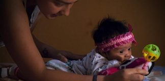 """Image taken on Feb. 27, 2016 shows Angela Martinez, playing with her daughter Dominic Andrade (R), who suffers microcephaly, in Quito, capital of Ecuador. Dominic Andrade, 4 months old, permanently receives therapy at home and on the facilities of a hospital due to microcephaly that has affected her since birth. Since the World Health Organization (WHO) issued a global alert against the virus, on Feb. 1, the authorities of several countries in America have strengthened the dissemination of messages in mass media for people to avoid the bite of """"Aedes aegypti"""" transmitter of Zika virus, dengue and chikungunya. However Zika virus continues to spread explosively in America, where there has been an increasing number of cases of microcephaly. (Xinhua file photo/Santiago Armas)"""