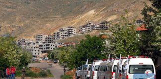 Ambulances of the Syrian Arab Red Crescent (SARC) wait on the outskirts of the rebel-held town of Madaya in northern Damascus, capital of Syria, on April 20, 2016. (Xinhua/Ammar)