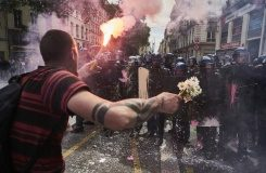 AFP / Jean-Philippe Ksiazek A man holds flowers and a torch as he faces riot police during a demonstration against the French government's planned labour reform in Lyon
