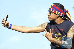Brazilian forward Neymar takes a selfie while attending FC Barcelona's celebration parade for winning the Spanish La Liga championship, in Barcelona, Spain, May 15, 2016. (Xinhua/Lino De Vallier)
