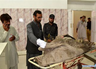 A doctor examines a dead body shifted to a civil hospital in southwest Pakistan's Quetta, May 22, 2016. Bodies of two people who are suspected to be killed in a Saturday U.S. drone strike in Pakistan have been shifted to a hospital in Quetta for DNA test. [Photo/Xinhua]