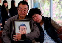 The parents of Wei Zexi, a computer science major at Xidian University in Shaanxi province who died of a rare form of cancer, wait outside a funeral home in Xianyang, Shaanxi, on April 13. [Wan Jia/ for China Daily ]