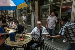 AFP/File / Anthony Wallace An employee (R) of a 'dai pai dong' (street food stall) passes a bowl of rice to a customer during a lunch break, in Hong Kong