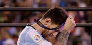 Argentina's Lionel Messi removes his medal after presentations following the Copa America Centenario championship soccer match, Sunday, June 26, 2016, in East Rutherford, N.J. Chile defeated Argentina 4-2 in penalty kicks to win the championship.