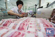 A clerk counts money. [Photo/Xinhua]