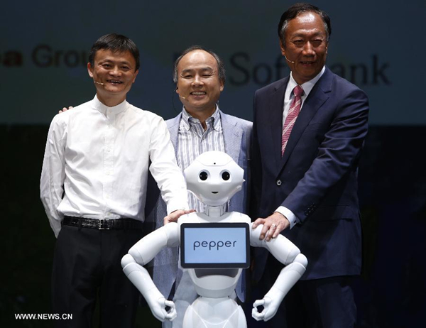 Jack Ma (L), Chairman of the Board of Alibaba Group, Softbank's president Masayoshi Son, and Terry Gou (R), founder and chairman of Foxconn, pose for photo with a humanoid robot