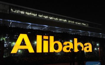 Two staff members walk past the logo of Alibaba at Alibaba Group's Xixi base in Hangzhou, capital of east China's Zhejiang Province on Nov. 12, 2014. [Photo/Xinhua]