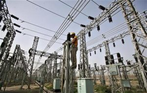 An employee works on electric pylons at a power station in Greater Noida on the outskirts of New Delhi June 8, 2012. REUTERS/Parivartan Sharma/Files