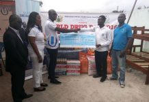 officials of Union Savings and Loans and NACOB presenting a dummy cheque to Mr Emmanuel Agyapong, the Director of DAFAREC, with the items in the background