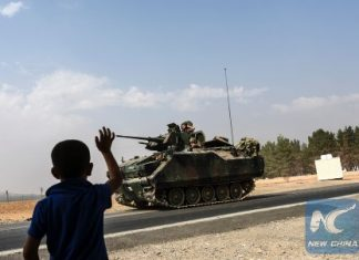 A Turkish boy waves to Turkish tank convoy driving into Syria from the Turkish Syrian border city of Karkamis in the southern region of Gaziantep, on August 26, 2016. (AFP/Xinhua)
