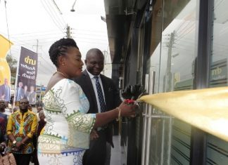 Mr John Awuah (left) being assisted by Madam Becky Hesse Lartey, Assembly Woman, Sakaman Electoral, to cutting the tape