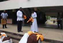 Madam Helen Ntoso, Volta Regional Minister presenting the uniforms to Mr Buadi