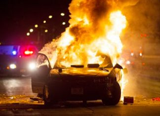 A car burns as a crowd of more than 100 people gathers following the fatal shooting of a man in Milwaukee, Saturday, Aug. 13, 2016. The Milwaukee Journal Sentinel reported that officers got in their cars to leave at one point, and some in the crowd started smashing a squad car's window, and another vehicle, pictured, was set on fire. The gathering occurred in the neighborhood where a Milwaukee officer shot and killed a man police say was armed hours earlier during a foot chase. (Calvin Mattheis/Milwaukee Journal-Sentinel via AP)