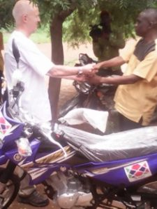 Professor Laurence David Gruer, presenting the brand new motorbike the District Coordinating Director, Alhaji Mahammed Issahaku.