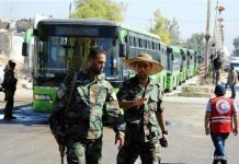 Syrian soldiers wait in front of buses parked to collect civilians who were evacuated from the rebel-held town of Muadamiyeh, in rural Damascus, capital of Syria, on Sept. 2, 2016. Nearly 300 civilians, who were originally from the town of Daraya for refuge, were evacuated from Muadamiyeh to government-controlled shelters in southern Damascus. (Xinhua file photo/Ammar)