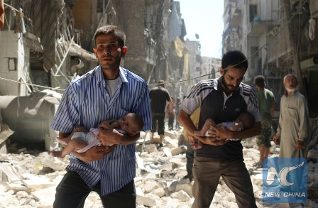 Syrian men carrying babies make their way through the rubble of destroyed buildings following a reported air strike on the rebel-held Salihin neighbourhood of the northern city of Aleppo, on September 11, 2016. (AFP/Xinhua)