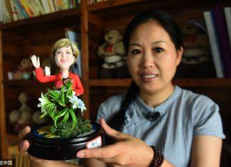 Wu Xiaoli holds a figurine of German Chancellor Angela Dorothea Merkel. (Photo: CFP)