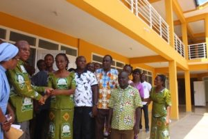 Mr Kpodo presenting keys to the classroom block to Madam Katsekpor