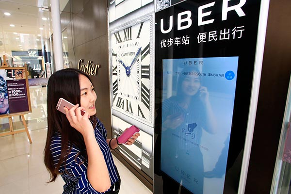 A woman uses Uber Technologies Inc's car-hailing service via an electronic screen in Tianjin.[Provided to China Daily]