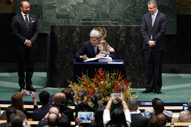 United States Secretary of State John Kerry signs the Paris climate agreement with his granddaughter at the United Nations headquarters in New York, April 22, 2016. (Xinhua/Li Muzi) (zw)