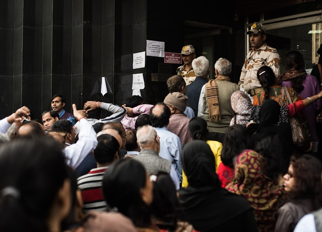 Security personnel keep order of the queue of people waiting to withdraw cash at the entrance of a bank in downtown New Delhi, India, Nov. 30, 2016. (Xinhua/Bi Xiaoyang) (zw)