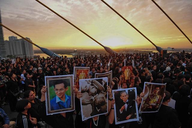 Well-wishers hold portraits of the late King Bhumibol Adulyadej during a merit-making ceremony on the Bhumibol Bridge in Bangkok, Thailand, Dec. 5, 2016. (Xinhua/Rachen Sageamsak) (zw)