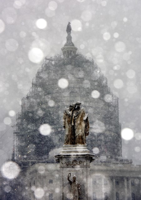 The Capitol and a statue are seen in snow in Washington D.C., the United States, Jan. 22, 2016. (Xinhua/Yin Bogu) (zw)